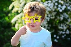 Criança pequena com vidros do partido do verão Criança do rapaz pequeno no feriado verde da mola da floresta tempo ensolarado Cri imagens de stock