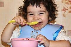 A criança pequena come-se com colher Fotografia de Stock
