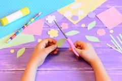 A criança pequena cria um cartão para a mamã etapa A criança guarda tesouras em suas mãos e corta uma folha do papel Imagens de Stock Royalty Free