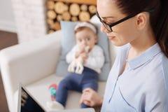 Criança pequena curiosa que olha sua mãe no trabalho Fotografia de Stock