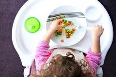 A criança pequena da criança come vegetais fotografia de stock royalty free