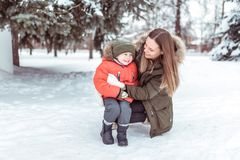 Criança pequena de 3-5 anos velho, de um inverno do menino no revestimento morno e do chapéu No inverno, na neve contra um fundo  fotografia de stock