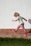 Criança pequena de passeio no jardim sobre a parede branca Imagem de Stock Royalty Free