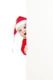 Criança pequena de Santa que olha do cartaz de trás Fotografia de Stock