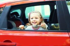 Criança pequena de sorriso do retrato que senta-se no carro vermelho Imagens de Stock