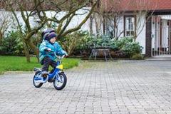 Criança pequena de três anos que montam na bicicleta no outono ou no winte Fotos de Stock