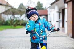 Criança pequena de três anos que montam na bicicleta no outono ou no winte Imagens de Stock