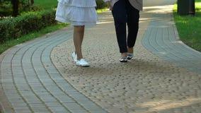 Criança pequena deficiente que vai para a caminhada com a enfermeira mais idosa perto da clínica médica filme