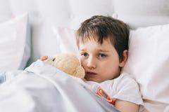 Criança pequena doente com temperatura na cama imagem de stock royalty free