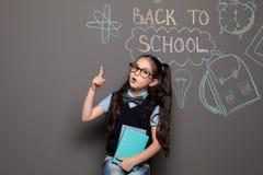 Criança pequena em desenhos próximos uniformes com texto DE VOLTA À ESCOLA imagem de stock royalty free