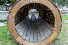 Criança pequena em um túnel de madeira em um campo de jogos Imagem de Stock