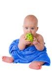 Criança pequena em uma esfera verde cortante de toalha azul Fotos de Stock Royalty Free