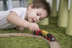 Criança pequena em uma sala de crianças colorida em um berçário ou em um pré-escolar menino da criança que joga com indicadores d Fotografia de Stock