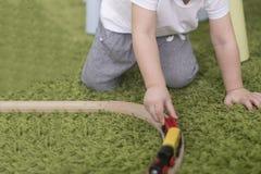 Criança pequena em uma sala de crianças colorida em um berçário ou em um pré-escolar menino da criança que joga com indicadores d Foto de Stock