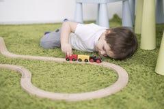 Criança pequena em uma sala de crianças colorida em um berçário ou em um pré-escolar menino da criança que joga com indicadores d Foto de Stock Royalty Free