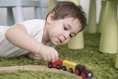 Criança pequena em uma sala de crianças colorida em um berçário ou em um pré-escolar menino da criança que joga com indicadores d Fotos de Stock
