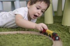 Criança pequena em uma sala de crianças colorida em um berçário ou em um pré-escolar menino da criança que joga com indicadores d Imagem de Stock Royalty Free