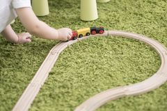 Criança pequena em uma sala de crianças colorida em um berçário ou em um pré-escolar menino da criança que joga com indicadores d Imagem de Stock