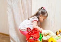 Criança pequena engraçada que joga com brinquedos imagens de stock royalty free