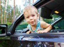 Criança pequena engraçada que olha da janela de carro aberta Fotos de Stock Royalty Free