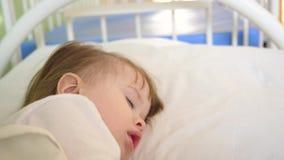 A criança pequena está dormindo no descanso Close-up O bebê de encantamento cai adormecido na cama branca em sua cama na sala em  filme