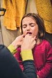 A criança pequena está gritando quando a mãe escovar seus dentes foto de stock