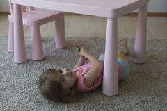 A criança pequena está jogando no tapete Fotografia de Stock Royalty Free