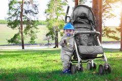 A criança pequena está perto de um carrinho de criança de bebê na floresta na grama verde no por do sol Criança feliz na natureza imagem de stock royalty free