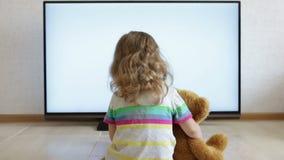 A criança pequena está sentando-se no assoalho e na tevê de observação vídeos de arquivo