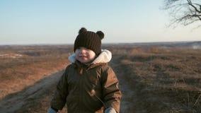 Criança pequena feliz, bebê que ri e que joga no outono na caminhada do parque fora video estoque
