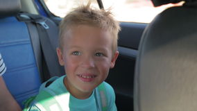 Criança pequena feliz com a trouxa que viaja pelo carro filme