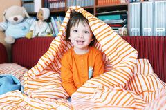 Criança pequena feliz na cama em casa Imagem de Stock Royalty Free