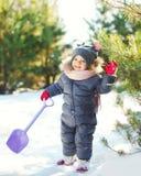 Criança pequena feliz que joga com o brinquedo da pá no inverno fotografia de stock royalty free