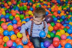 Criança pequena feliz que joga no campo de jogos plástico colorido das bolas Foto de Stock