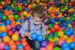 Criança pequena feliz que joga no campo de jogos plástico colorido das bolas Fotos de Stock