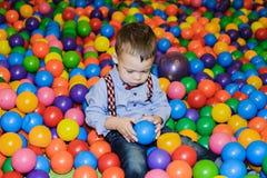 Criança pequena feliz que joga no campo de jogos plástico colorido das bolas Fotografia de Stock