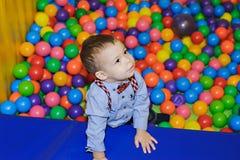 Criança pequena feliz que joga no campo de jogos plástico colorido das bolas Fotos de Stock Royalty Free