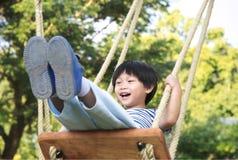 Criança pequena feliz que ri e que balança em um balanço Imagem de Stock Royalty Free