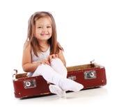 Criança pequena feliz que senta-se em uma mala de viagem. Curso Fotografia de Stock Royalty Free