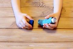 A criança pequena guarda o inalador da asma em suas mãos Tratamento da inalação de doenças respiratórias Conceito da alergia e da imagem de stock royalty free