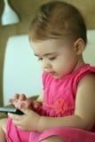 A criança pequena joga com o smartphone que senta-se no sofá Imagens de Stock