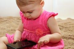 A criança pequena joga com o smartphone que senta-se no sofá Fotografia de Stock Royalty Free