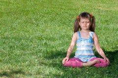 A criança pequena meditate no asana na grama verde imagens de stock royalty free