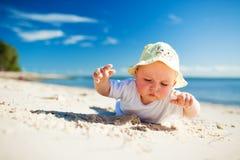 Criança pequena na areia de exploração da praia imagens de stock royalty free