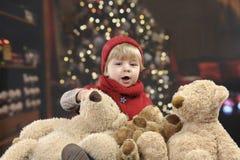 Criança pequena na frente de uma árvore de Natal fotos de stock royalty free
