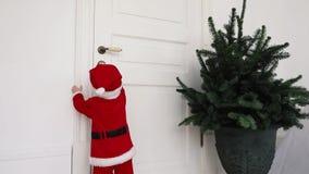 Criança pequena na tentativa do terno de Santa à casa do estar aberto vídeos de arquivo