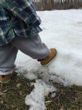 Criança pequena nas botas do trabalho que jogam na neve Imagem de Stock Royalty Free