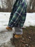 Criança pequena nas botas do trabalho que jogam na neve Imagens de Stock Royalty Free