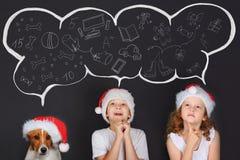 Criança pequena no chapéu de Sante, sonhando dos presentes mágicos do Natal Fotografia de Stock