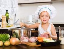 Criança pequena no chapéu do cozinheiro que cozinha a sopa Imagens de Stock Royalty Free